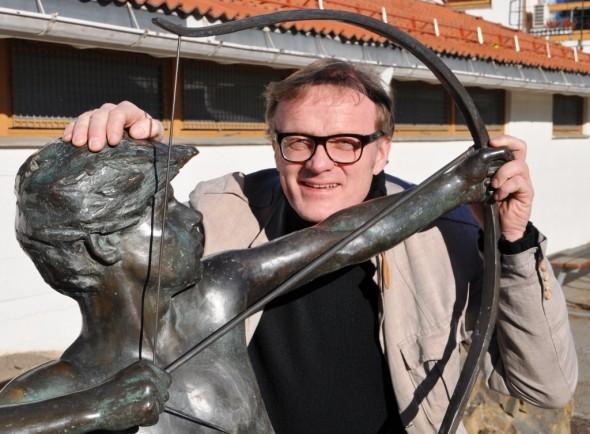 """Rektor poserer ved skolens kjære skulptur: """"Bueskytteren"""""""