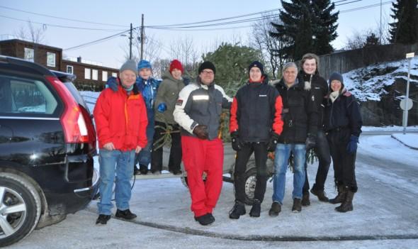 """En travel gjeng tar seg to minutters fotopause ved Meny. Nok en tilhenger er fylt opp med """"gamle"""" juletrær."""